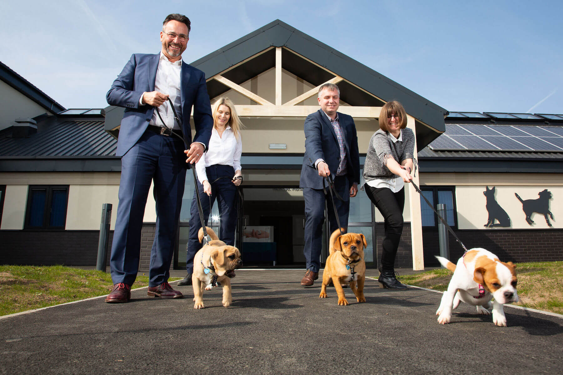 Walkies! Integra Buildings Managing Director Gary Parker, left, and Commercial Director Chris Turner with Centre Manager Ella Carpenter, second left, and Rachel Jenkins, of Williams Architects, take some of RSPCA Radcliffe's residents for a stroll.